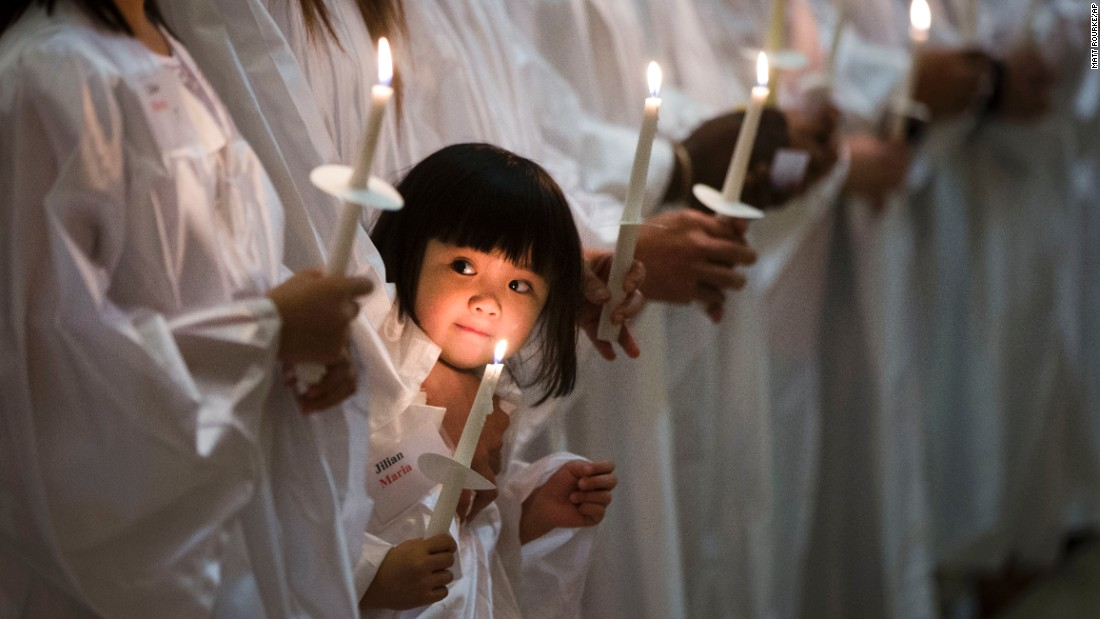 <strong>April 4:</strong> Jillian Nguyen, 3, stands with others as they are baptized into the Catholic faith in Philadelphia.