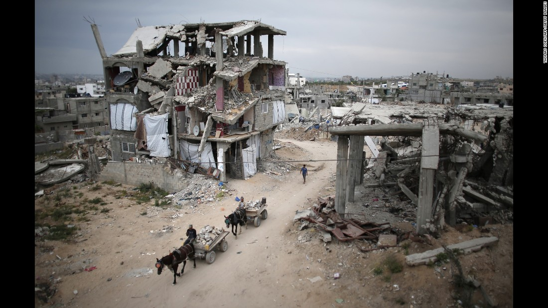 <strong>May 11:</strong> Palestinians ride their donkey carts past destroyed buildings in Gaza City. The buildings were destroyed in 2014 during the 50-day war between Israel and Hamas.