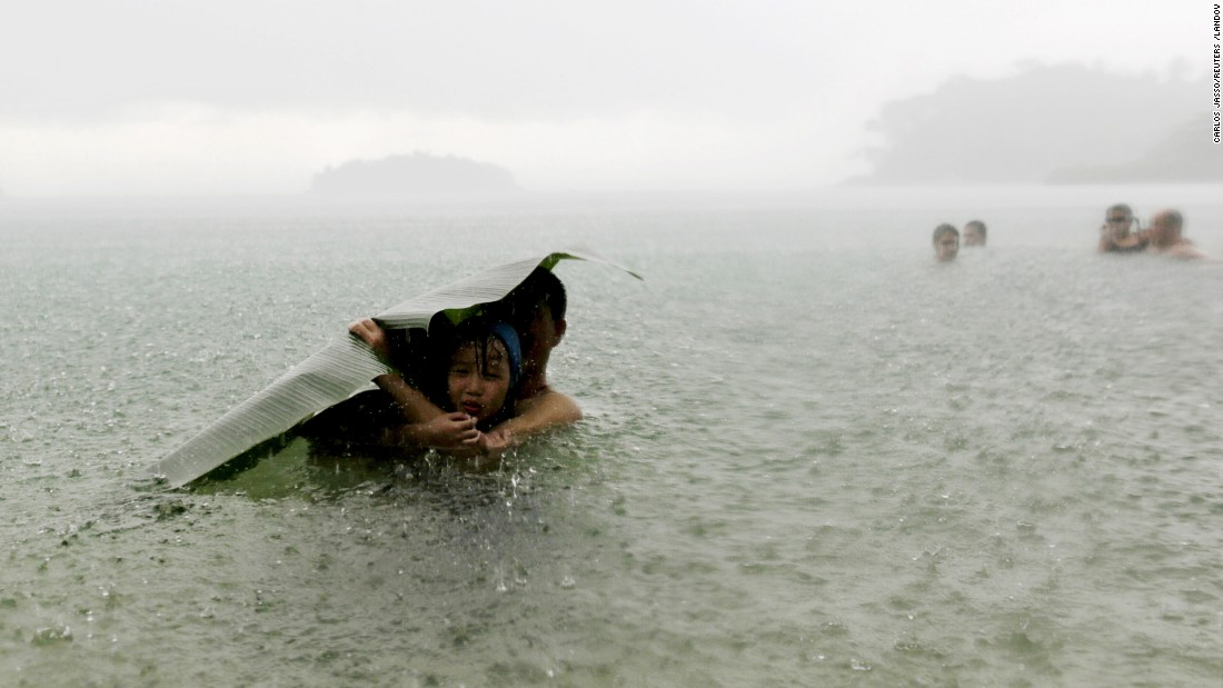 <strong>October 17:</strong> A man and girl use a banana leaf to cover themselves from the rain as they wade in the sea on the outskirts of Colon, Panama.