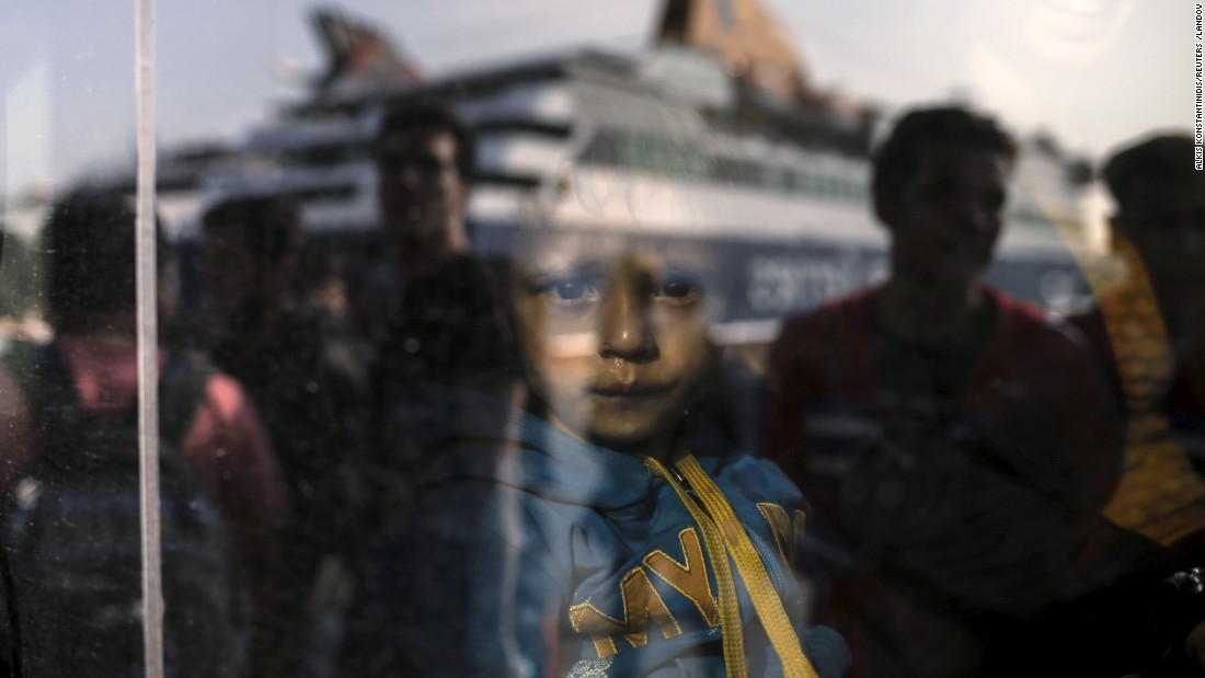 <strong>October 19:</strong> A young boy is seen through a bus window as refugees and migrants arrive at the port of Pireaus, Greece.