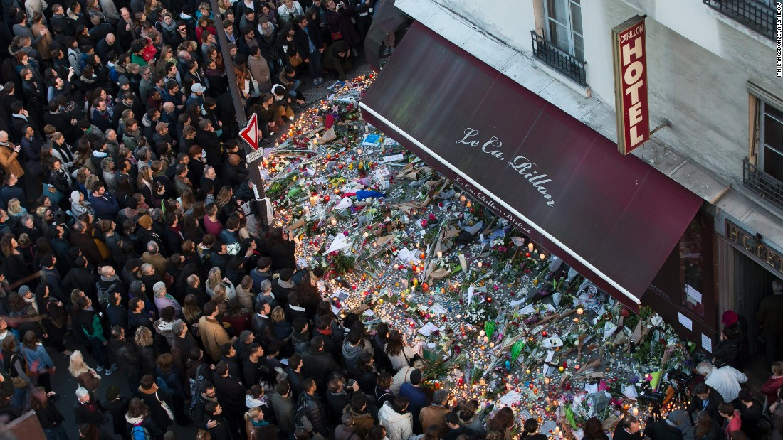 <strong>November 15:</strong> A large crowd gathers to lay flowers and candles in front of the Carillon restaurant, one of the establishments in Paris targeted by terrorists in the November 13 attacks.