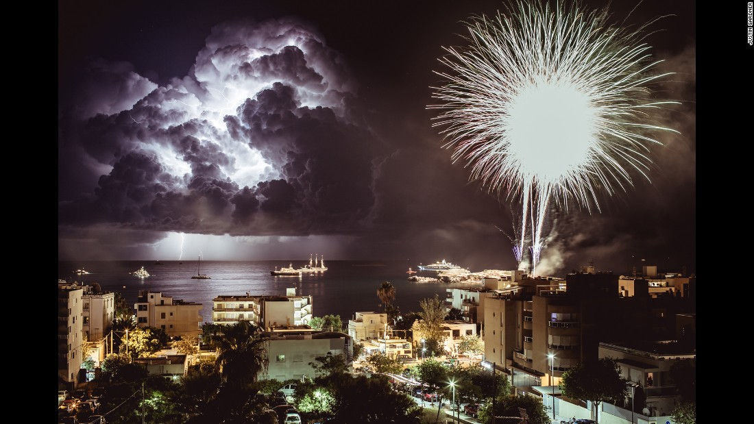 <strong>August 16:</strong> Fireworks explode in Figueretas, Spain, as lightning flashes over the sea.
