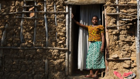 Christina John (14 years old) stands outside her house where she lives with her husband and her mother-in-law in Rebu village in Tarime district of Mara region in Tanzania. She was married when she was little over 13 years old. She managed to finish grade 7 before she was married off.