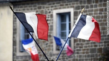 "A picture taken on November 27, 2015, shows French national flags put on a window and in the streets in Hede-Bazouges, north of Rennes, during the National Tribute to the 130 people killed in the November 13 Paris attacks. President Francois Hollande will lead a solemn ceremony in honour of the victims. Families of those killed in France's worst-ever terror attack, claimed by the Islamic State (IS) group, will join some of the wounded at ceremonies at the Invalides, the gilded 17th-century complex in central Paris that houses a military hospital and museum and Napoleon's tomb.The tribute will be ""National and Republican,"" an official at the Elysee presidential palace said, referring to the French republic's creed of liberty, equality and fraternity. AFP PHOTO / DAMIEN MEYER / AFP / DAMIEN MEYER        (Photo credit should read DAMIEN MEYER/AFP/Getty Images)"