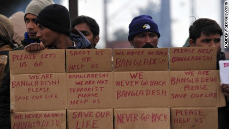 Men from Bangladesh stuck at the Greek-Macedonian border hold up signs pleading for help