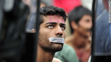 A man tapes his mouth shut in protest, after being told to turn back in Gevgelija, Macedonia