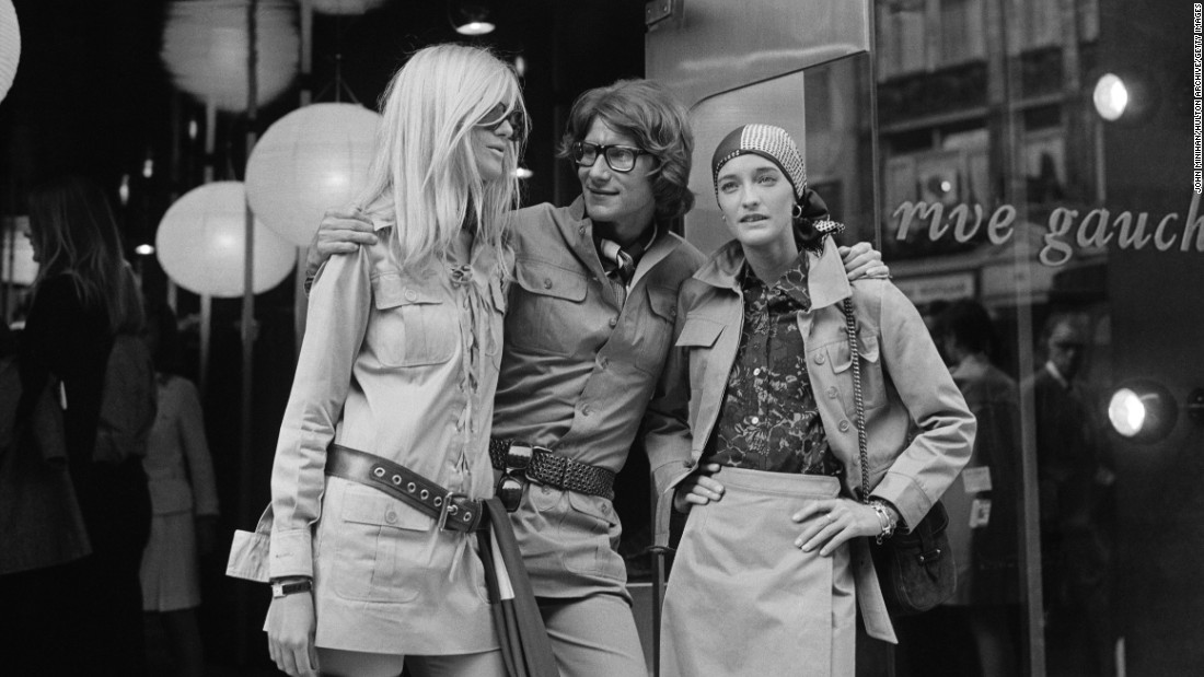 Yves Saint Laurent was at the creative helm of Christian Dior before branching out to start his own eponymous label in 1960. <br /><em><br />Yves Saint with friends and muses Betty Catroux and Loulou de la Falaise outside of his Paris Rive Gauche shop, 1969</em>