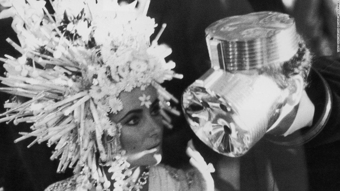 Gaultier cut his teeth working in the atelier of designer Pierre Cardin, known for his futuristic aesthetic. <br /><em><br />Elizabeth Taylor (left) with designer Pierre Cardin, wearing a headress of his own design in 1967</em>