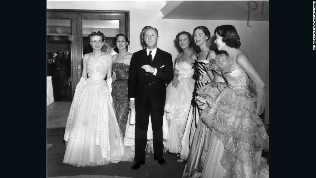 "Couturier Christian Dior caused an international frenzy in 1947 when he introduced the ""New Look,"" an hourglass silhouette that had all but disappeared from fashion during WWII. <br /><em><br />Christian Dior with models at London's Savoy Hotel, 1950 </em>"