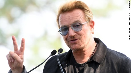 Bono holds up a peace sign during a dedication ceremony for a giant tapestry, from Amnesty International, in honor of John Lennon on Ellis Island July 29, 2015, in New York. Photo by DON EMMERT/AFP/Getty Images