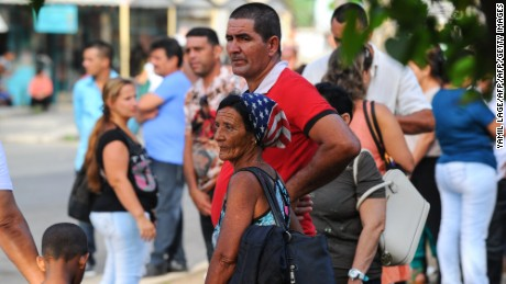 Cubans congregate at a square outside the US interests section in Havana to apply for visas, on July 1, 2015. President Barack Obama is expected to unveil today a breakthrough deal with Cuba to reopen embassies in Washington and Havana, officials said, in a major step toward ending decades of Cold war enmity. Cuban President Raul Castro and Obama agreed in December to start formal talks over restoring relations, after months of secret talks between aides. Diplomatic ties have been frozen since 1961.  AFP PHOTO / YAMIL LAGE        (Photo credit should read YAMIL LAGE/AFP/Getty Images)