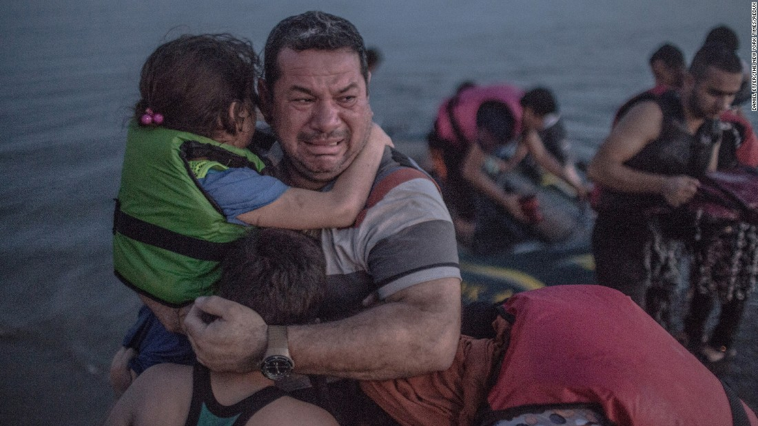 <strong>August 15:</strong> A refugee, holding his son and daughter, cries tears of joy after their boat arrived on the Greek island of Kos. The island in the Aegean Sea has been overwhelmed by refugees.