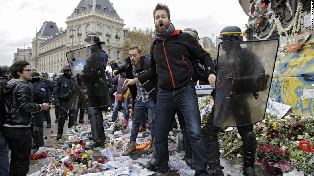 A man is detained November 29 by police at the Place de la République, where the candles and flowers were set in memory of the victims of the Paris terror attacks earlier in the month.