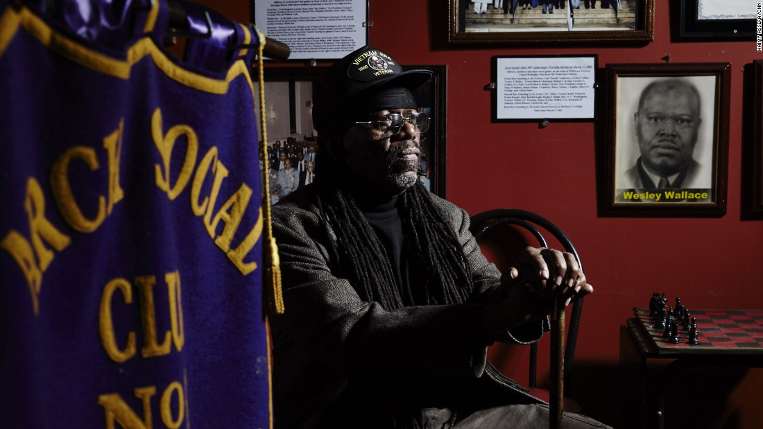 "Kaleb Tshamba belongs to the historic Arch Social Club. More than 100 years old, the club has been traditionally African American and for males only. ""We are one of the only historic black places left in Baltimore,"" Tshamba said. The club sits across the street from the CVS store that was burned during the April riot. Tshamba and other members of the club participate in the 300 Men March, which calls for a stop to violence. A sign on the front of the club's building reads, ""We must stop killing each other."""