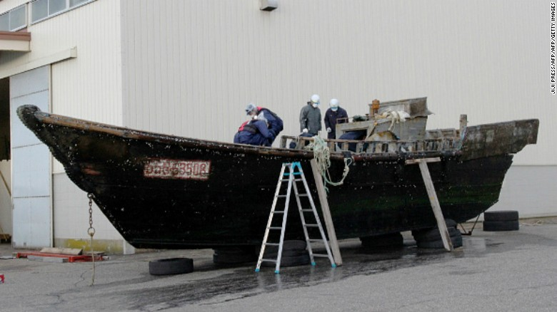 This picture taken on November 24, 2015 shows coast guard officials investigating a wooden boat at the Fukui port in Sakai city in Fukui prefecture, western Japan after the ship was found drifting off the coast of Fukui. Japan is investigating nearly a dozen suspicious boats recently found drifting off the country's coastline, some with decaying bodies aboard, officials said on November 27, as media speculated they came from North Korea. At least 11 cases involving wooden boats -- some badly damaged -- with 20 bodies on board have been reported during October and November.