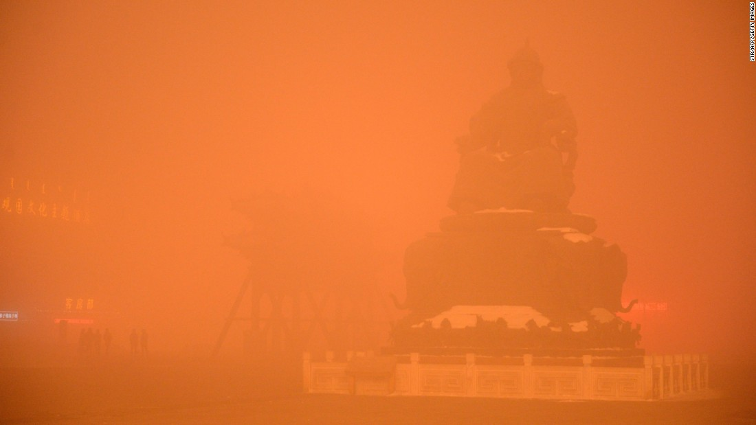 A Genghis Khan statue is obscured by a cloak of orange-tinged smog on November 29, 2015 in Hohhot, capital of Inner Mongolia, China.