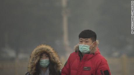 In this Saturday, Nov. 28, 2015, file photo, people wearing face masks walk across Tiananmen Square on a day with poor air quality in Beijing. Air pollution in Beijing reached hazardous levels on Saturday as smog engulfed large parts of the country despite efforts to clean up the foul air.