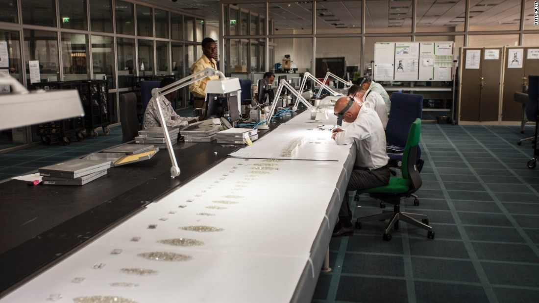 De Beers employees inspect diamonds aggregated from the company's global supply in Gaborone, Botswana. The company moved 82 experts and their families from London to set up the facility in 2013.