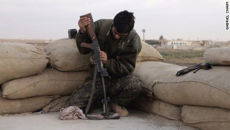 A Kurdish soldier cleans his weapon.