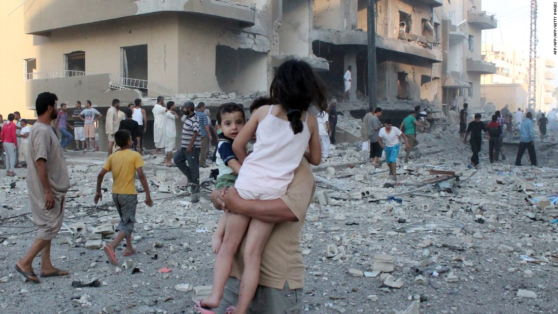 A man carries two children away from the scene of an explosion in Raqqa on August 7, 2013.