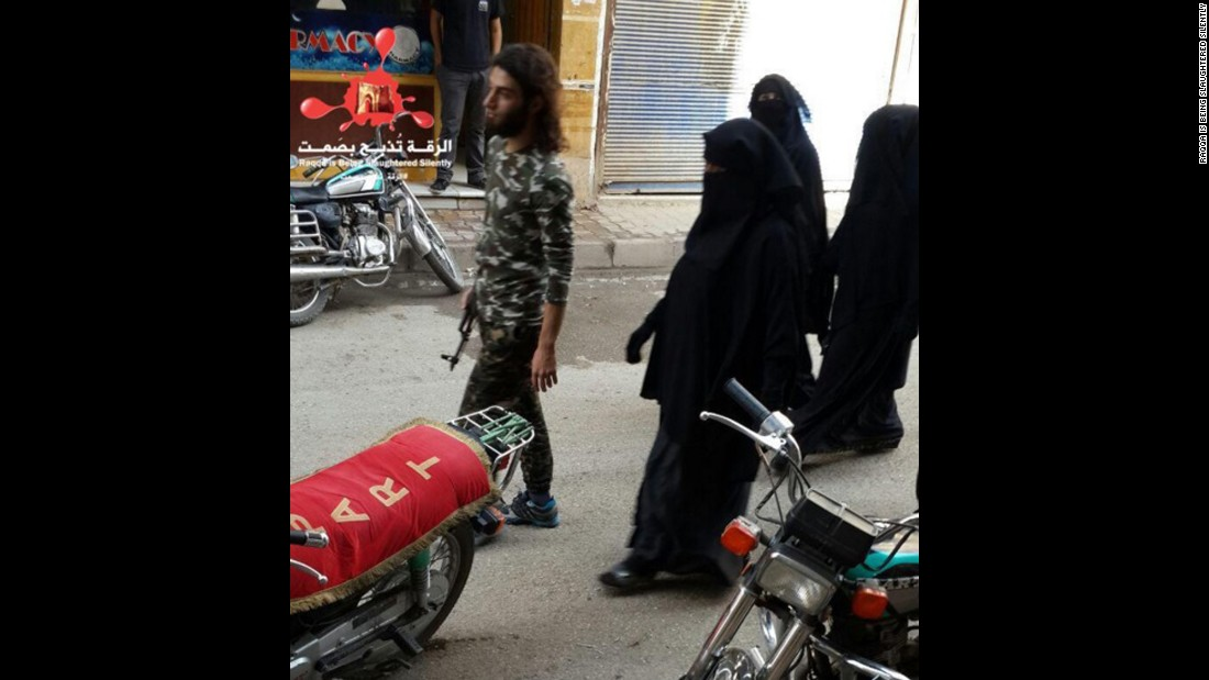 In this photo from November 6, 2015, an ISIS fighter walks along a street in Raqqa with his 3 wives walking behind him, according to RBSS.