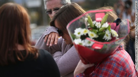 SAN BERNARDINO, CA - DECEMBER 03:  A mourner cries as she brings flowers to a road block outside of the Inland Regional Center on December 3, 2015 in San Bernardino, California. Police continue to investigate a mass shooting at the Center that left at least 14 people dead and another 17 injured.  (Photo by Justin Sullivan/Getty Images)