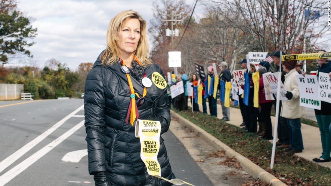 "Martina Leinz, 53, stands in front of the National Rifle Association headquarters in Fairfax, Virginia, along with other gun control advocates on November 14, 2015. Leinz has been to more than two dozen NRA protests, beginning with the first one, held after the December 14, 2012, massacre in Newtown, Connecticut. Leinz was a junior in high school in 1979 when the effects of gun violence hit home. Her classmate, Brenda Spencer, used a high-caliber rifle to open fire on an elementary school in San Diego. She killed the principal and a janitor who came to his aid and wounded eight children. ""It was horrifying to me that somebody who I knew could do something like that,"" Leinz says. ""It opened my eyes to the dangers."""