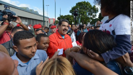 Venezuela's President Nicolas Maduro (C) arrives at the polling station to vote in the legislative election, in Caracas, on December 6, 2015. Venezuelans voted Sunday in tense elections that could see the opposition seize legislative power from the socialist government and risk sparking violence in the oil-rich, cash-poor nation.    AFP PHOTO/LUIS ROBAYO / AFP / LUIS ROBAYO        (Photo credit should read LUIS ROBAYO/AFP/Getty Images)