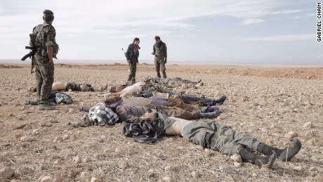 After battle, Kurdish fighters -- women among them -- lift the shirts of dead ISIS fighters to check for suicide vests.