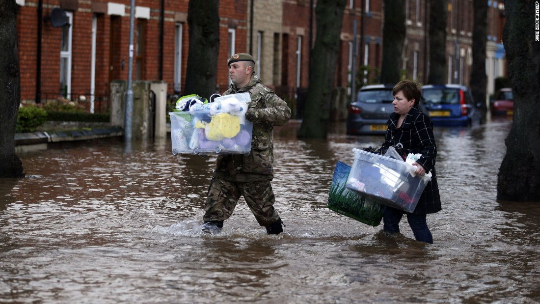 A member of the armed forces helps a resident move their belongings through the flood water in Carlisle, December 6.