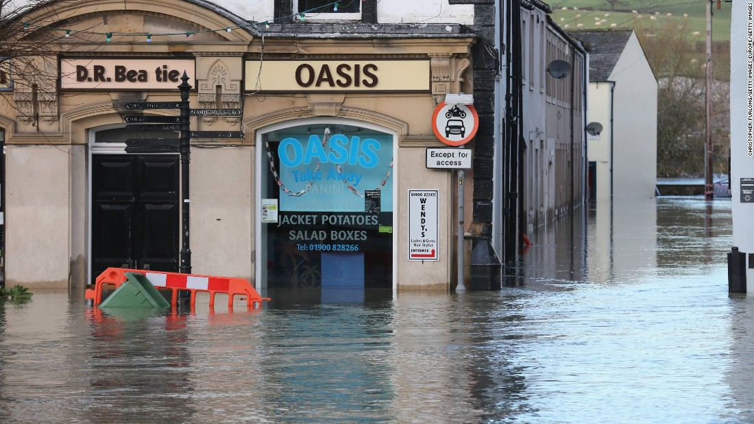 Water rises near a fast food store December 6 in Cockermouth, which sits at the confluence of the River Cocker and River Derwent.