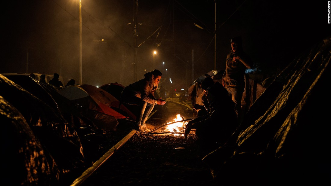 Migrants warm themselves around a fire at the border.