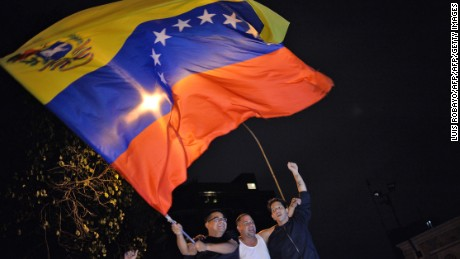 TOPSHOT - Venezuelan opposition supporters celebrate the results of the legislative election in Caracas, on the early morning December 7, 2015. Venezuela's opposition won --at least--a majority of 99 out of 167 seats in the state legislature, electoral authorities said Monday, the first such shift in power in congress in 16 years.   AFP PHOTO/LUIS ROBAYO / AFP / LUIS ROBAYO        (Photo credit should read LUIS ROBAYO/AFP/Getty Images)