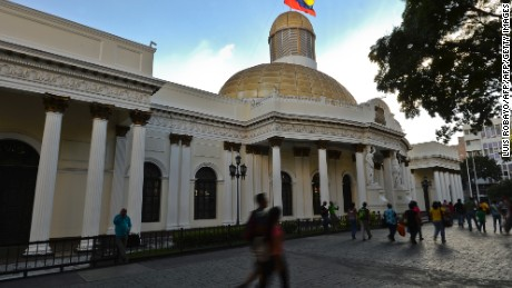 People walk past the National Assembly building in Caracas, on December 7, 2015. Venezuela's jubilant opposition vowed Monday to drag the oil-rich country out of its economic crisis and free political prisoners after winning control of congress from socialist President Nicolas Maduro. AFP  PHOTO/Luis Robayo / AFP / LUIS ROBAYO        (Photo credit should read LUIS ROBAYO/AFP/Getty Images)