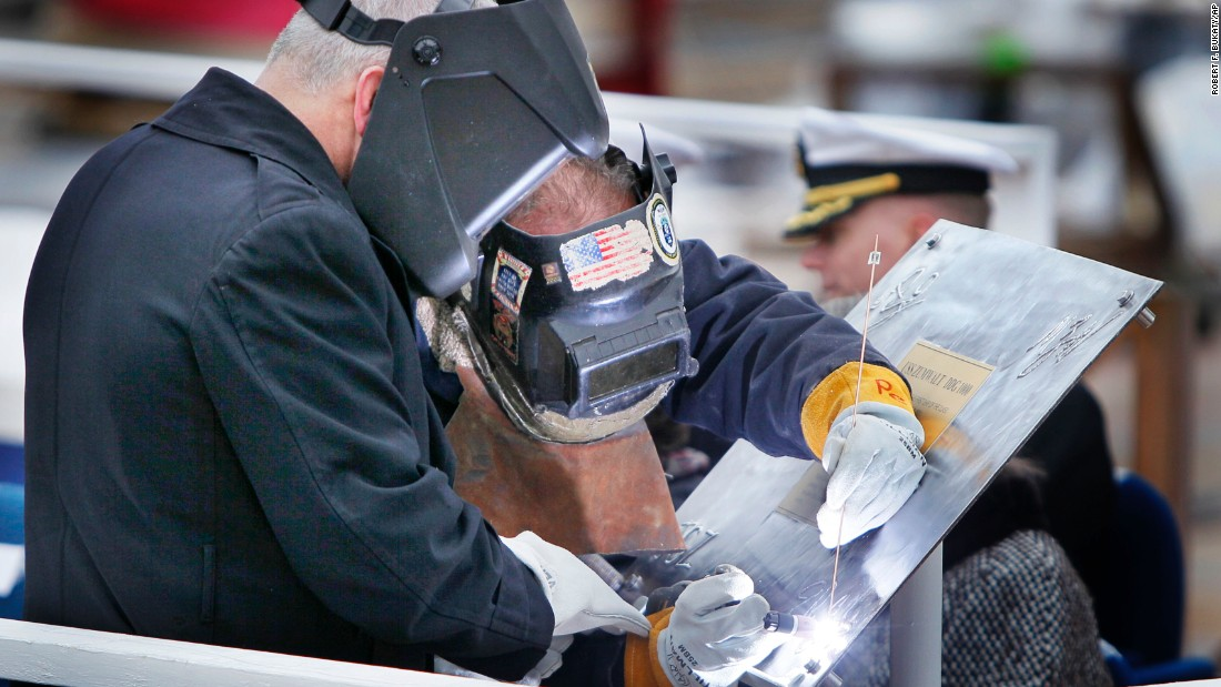 Retired Marine Corps Lt. Col. James G. Zumwalt, left, assists welder Carl Pepin as he inscribes a steel plate at a keel laying ceremony at Bath Iron Works on Thursday, November 17, 2011.