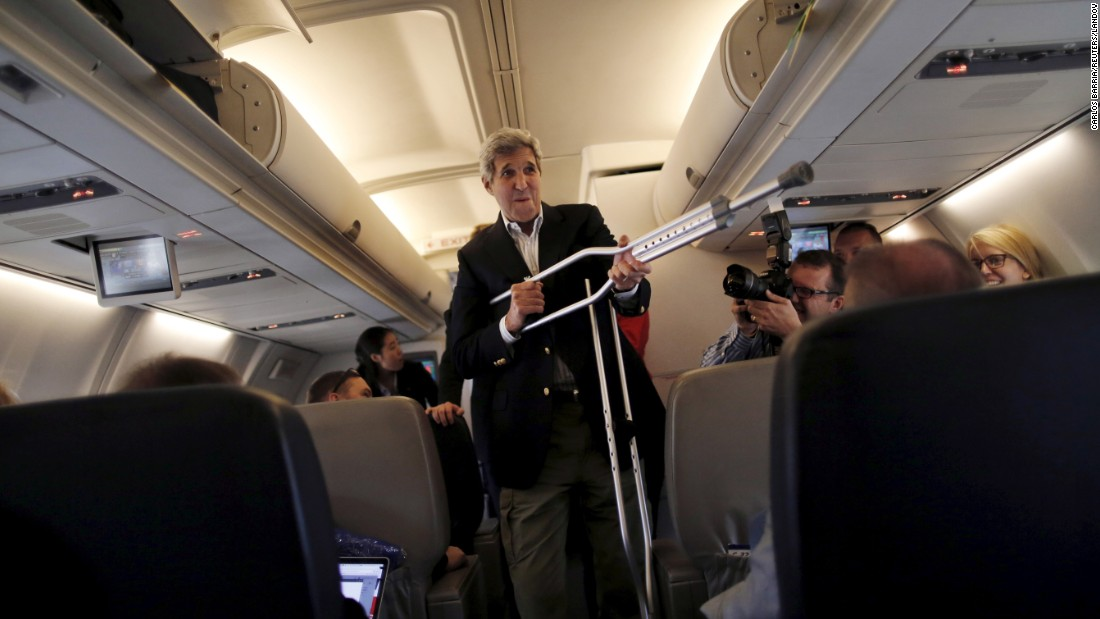 U.S. Secretary of State John Kerry plays with his crutches as he talks to reporters aboard a plane in Maryland on Friday, June 26. Kerry broke his leg riding a bike in May.