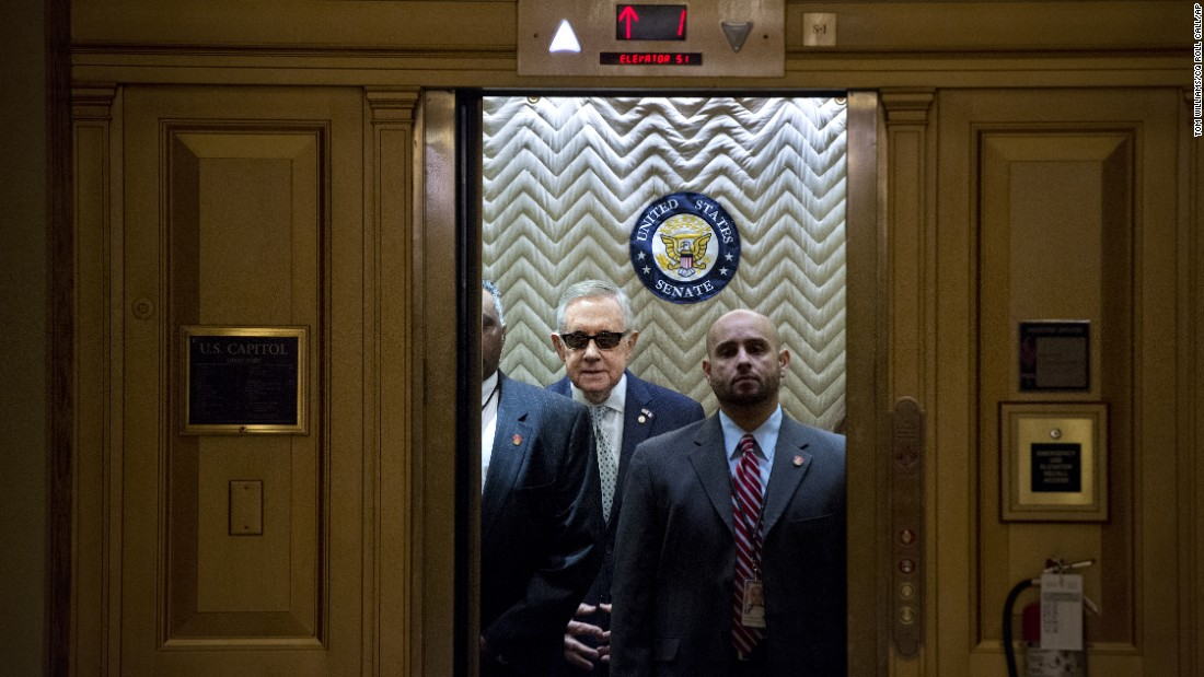 Senate Minority Leader Harry Reid, in the sunglasses, boards an elevator at the Capitol after signing a condolence book Tuesday, November 17, for victims of the Paris terrorist attacks.