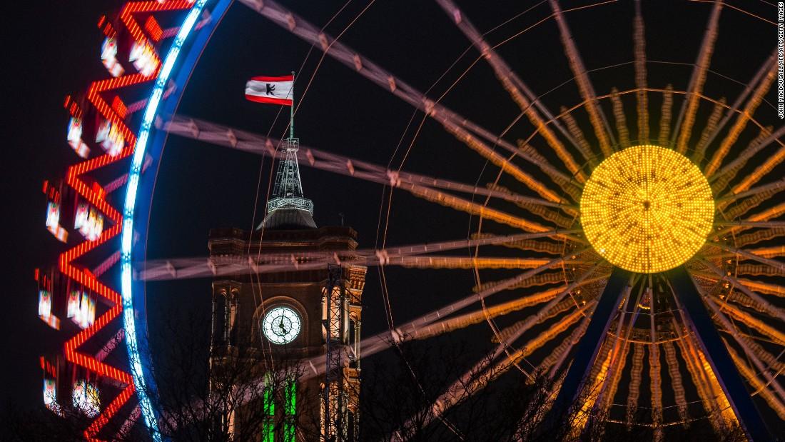 Berlin's town hall is seen through a revolving Ferris wheel at a Christmas market.