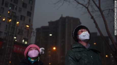 A young girl and a woman wear masks as they watch a giant video screen outside a shopping mall on a polluted day in Beijing on December 9, 2015.   Pollution red alerts spread to more Chinese cities, state media reported on December 9, as Beijing entered its third day of heavy smog, with officials warning poor conditions could last until Saturday in some places.  / AFP / GREG BAKERGREG BAKER/AFP/Getty Images