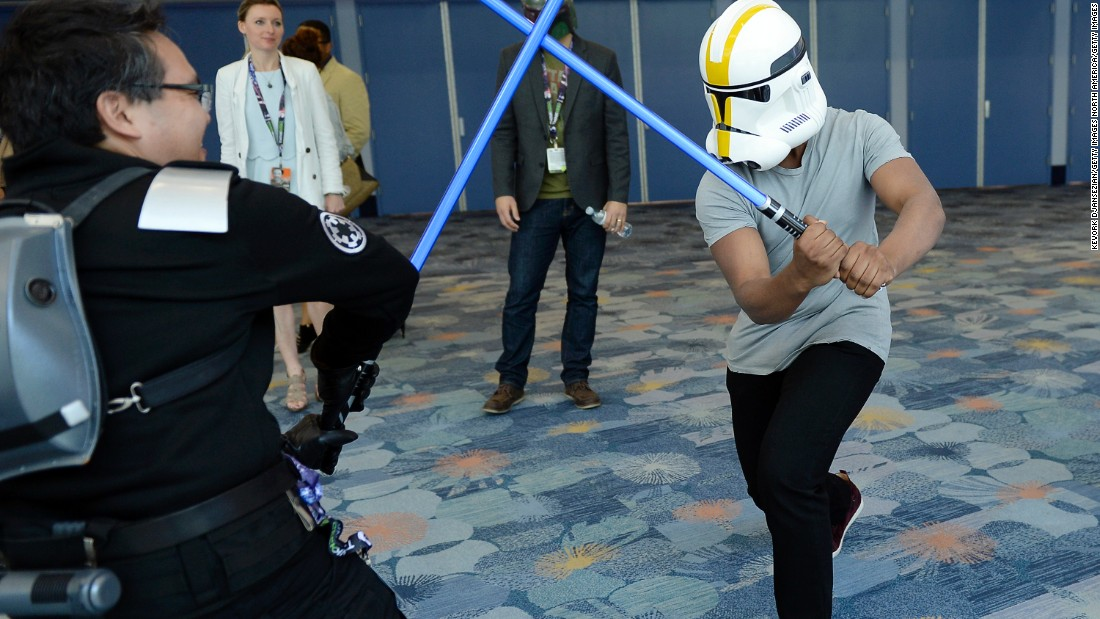 """The Force Awakens"" cast member John Boyega wearing a Stormtrooper helmet to disguise his identity engages a unknowing fan in a lightsaber dual during the kick-off event of Disney's Star Wars Celebration 2015."