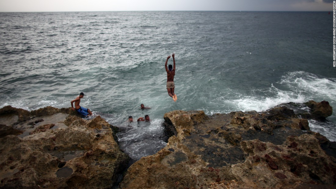 Locals swim along the Malecon coastal area in Havana.