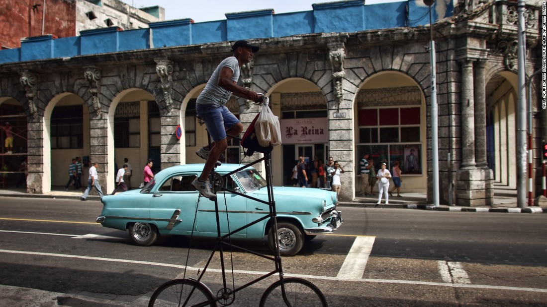 A man rides his modified bicycle past a vintage American car in Havana.
