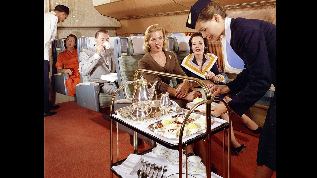 Afternoon tea with full silver service might seem old fashioned, but check out the woman in the window seat. That dress with built-in napkin is jet-age technology in action.
