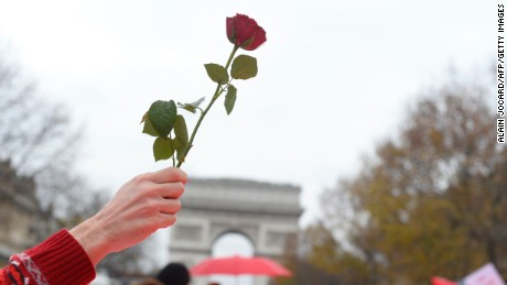 An activist holds up a rose as other activists gather to form a giant red line during a demonstration near the Arc de Triomphe at the Avenue de la Grande armee boulevard in Paris on December 12, 2015, as a proposed 195-nation accord to curb emissions of the heat-trapping gases that threaten to wreak havoc on Earth's climate system is to be presented at the United Nations conference on climate change COP21 in Le Bourget, on the outskirts of Paris.  AFP PHOTO / ALAIN JOCARD / AFP / ALAIN JOCARD        (Photo credit should read ALAIN JOCARD/AFP/Getty Images)