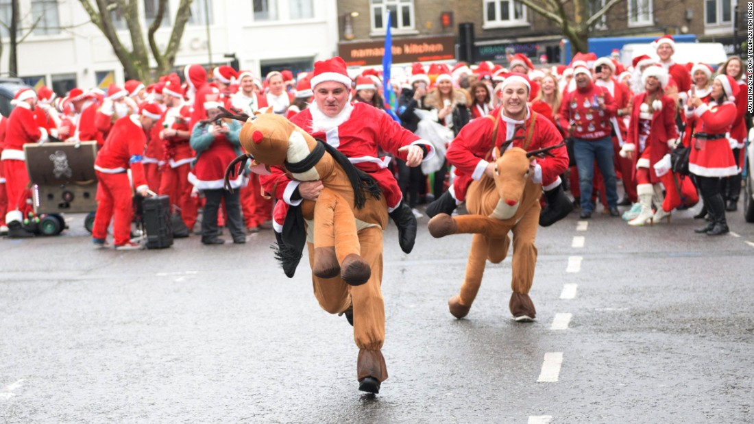 Two participants in Santa and reindeer costumes race each other during a SantaCon event in London, England.