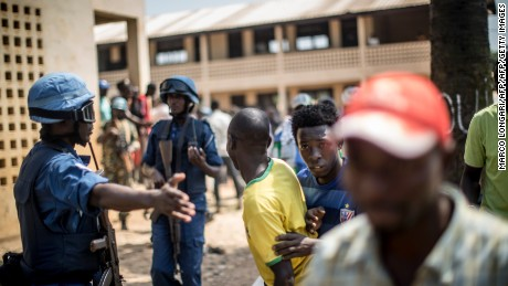 Soldiers direct Burundi civilians to cover as gunfire is directed toward a school where voters were gathered in December.