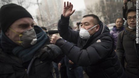 Chinese police push away journalists and supporters of human rights lawyer Pu Zhiqiang demonstrating near the Beijing Second Intermediate People's Court in Beijing on December 14, 2015. One of China's most celebrated human rights lawyers went on trial December 14 over online comments critical of the ruling Communist Party, as police scuffled with supporters and journalists gathered outside the courthouse. AFP PHOTO / FRED DUFOUR / AFP / FRED DUFOUR        (Photo credit should read FRED DUFOUR/AFP/Getty Images)