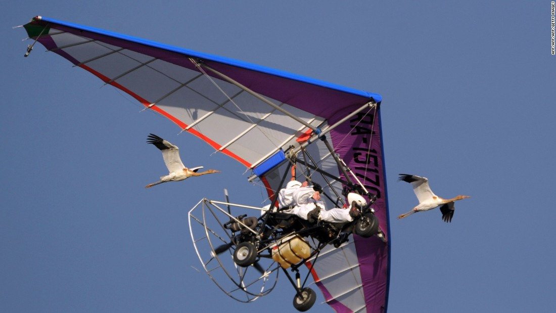Here he is pictured piloting a motorized hang glider while flying with cranes that have taken to the machine as their leader.
