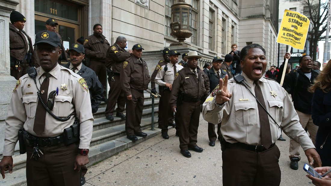 Law enforcement officers try to calm down a crowd gathered in front of the courthouse on December 16. Gray died in April after sustaining a neck injury while in police custody.