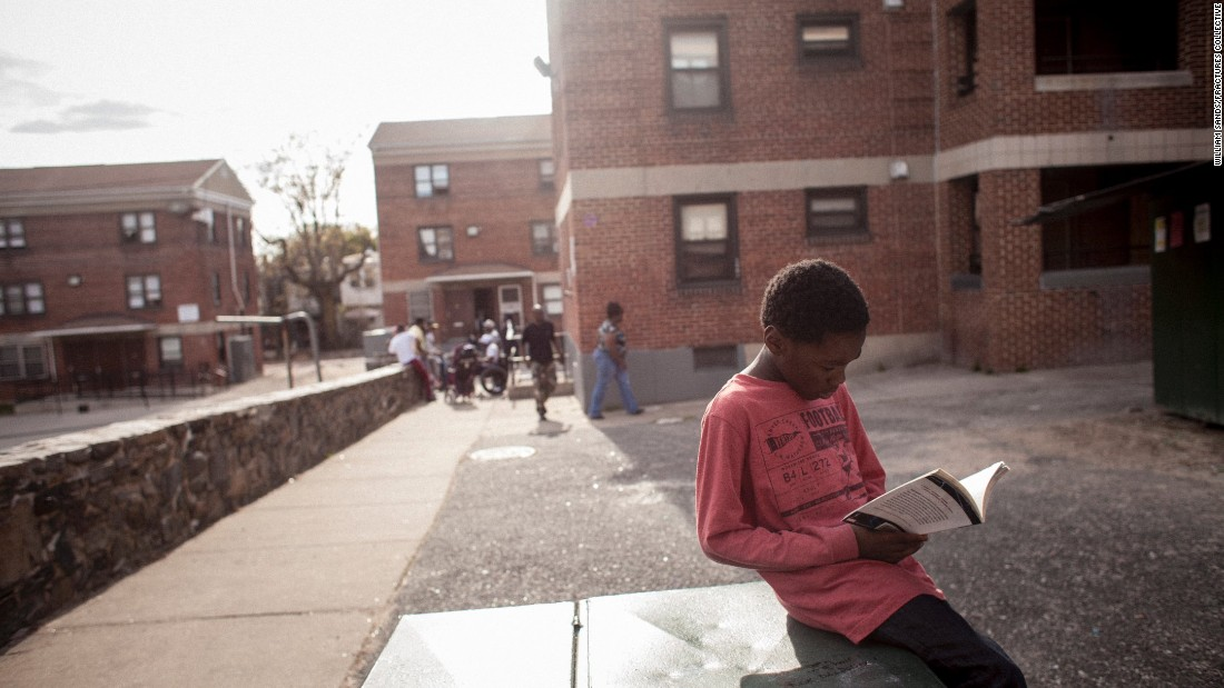 A boy reads a book he picked out during a giveaway organized by members of Out for Justice, a nonprofit advocacy group run by ex-prisoners. The group organizes clothing drives for the poor and a weekly barbecue for the homeless. They are also active in local politics.